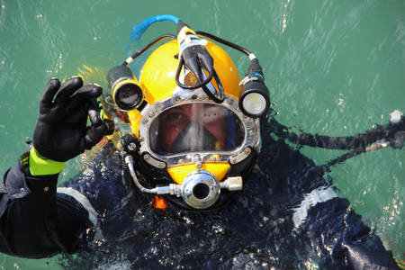 diver in the water in a diving suit and helmet ready to dive and showing sign ok Banco de Imagens