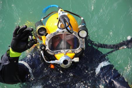 duiker in het water in een duikpak en helm klaar om te duiken en het tonen van ok teken Stockfoto