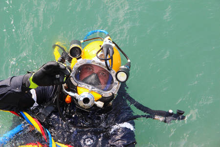 diver in the water in a diving suit and helmet ready to dive and showing sign ok Stok Fotoğraf