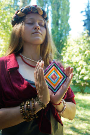 Girl with brown hair in a clothes in boho style, she is standing on a glade among the trees and holding a handmade wicker native american mandala