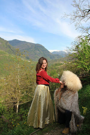 Photo of a man in furs and a traditional georgian fur hat kisses a hand of a young brunette woman in a traditional georgian costume stands on a background of mounains covered in a freen forest