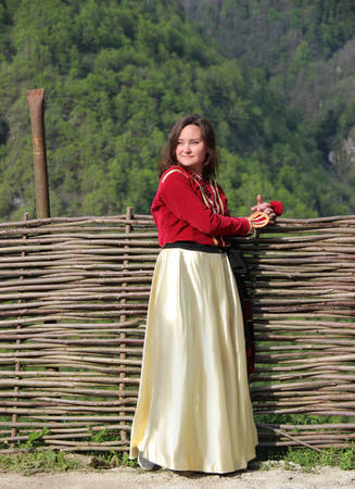 Photo of young brunette woman in a traditional georgian costume stands near a wicker fence on a background of mounains covered in a freen forest