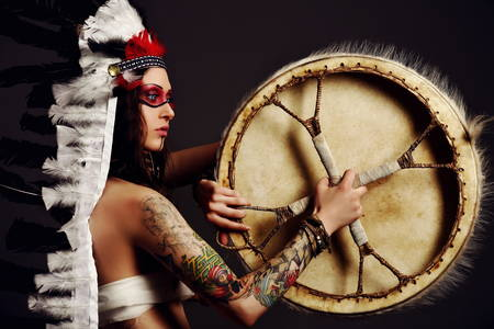 Beautiful woman in native american costume with tambourine and roach on her head posing in a studio