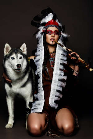 beautiful woman in native american costume posing in a studio with hasky dog stock photo