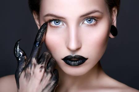 Black lips. Halloween Makeup. Luxury beautiful woman with dark lipstick and claws. Beauty stylish girl