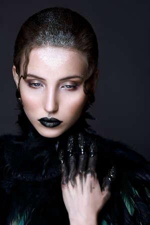 Black lips. Halloween Makeup. Luxury beautiful woman with dark lipstick and black feather collar. Beauty stylish gothic girl Stock Photo