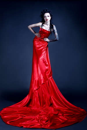 Beautiful young girl with a tattoo on her shoulder in a red dress posing in a studio on a dark background. Gothic image. Banque d'images - 96899057