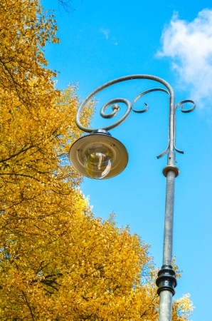 large iron lantern on the background of sky and yellow leaves in autumn photo