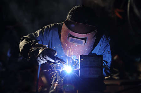 welding metal: skilled working factory welder  Stock Photo
