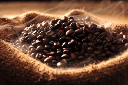 granos de cafe: Fresh granos tostados de café con humo saliendo de la bolsa