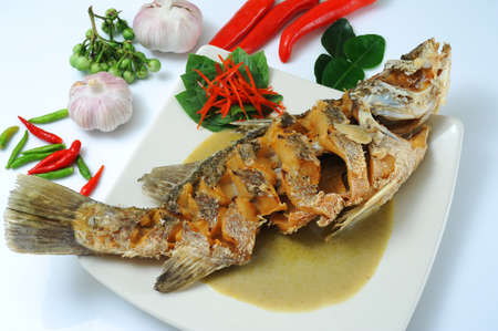 Deep fried fish in green curry sauce photo