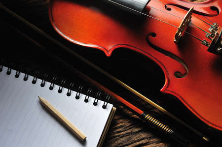 Violin and notebook on wooden table Stock Photo - 14255770