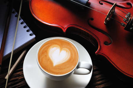 heart break: Latte art and violin on wooden table