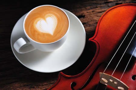 Latte art and violin on wooden table photo
