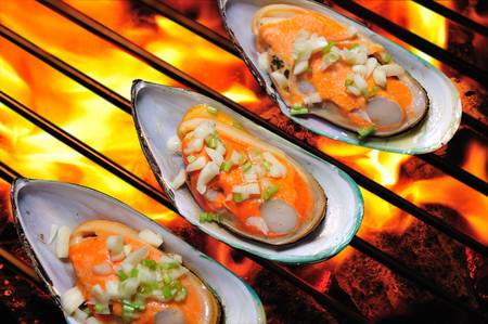 mussels: Grilled mussels topped with butter, garlic and parsley on flaming grill