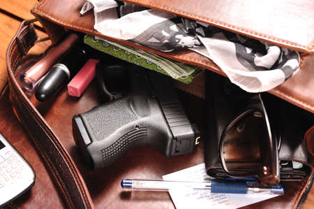 and carry on: a gun in a purse Stock Photo