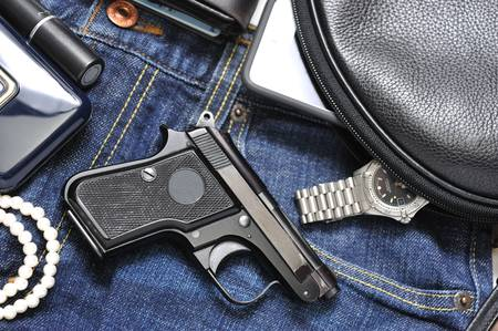 automatic pistol: A woman s purse and gun and accessories Stock Photo