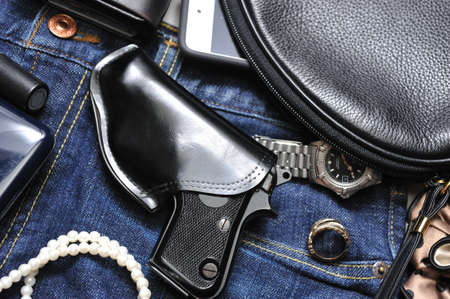 and carry on: A woman s purse and gun and accessories Stock Photo