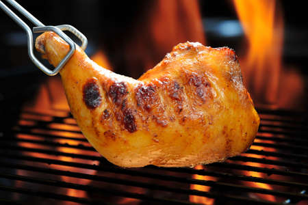 muslos: Muslo de pollo a la parrilla en la parrilla llameante