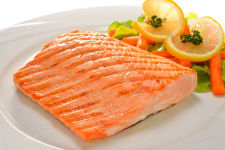 salmon steak: grilled salmon with vegetables on white plate