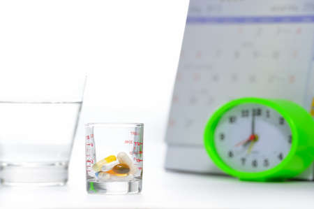 Pills and a glass of water with a clock and calend photo