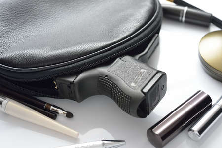A woman s purse and gun and accessories  photo