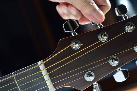 guitar tuner:  Hand tuning a guitar from headstock Stock Photo