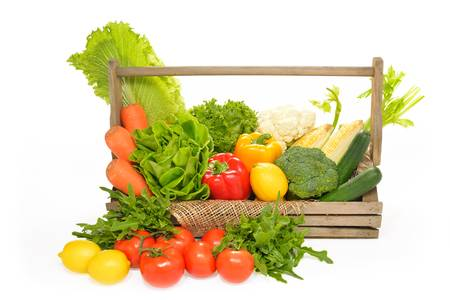 fruits and vegetables in wooden basket on white background photo