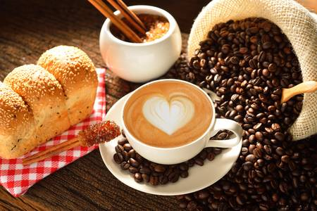 A cup of cafe latte with coffee beans and bread