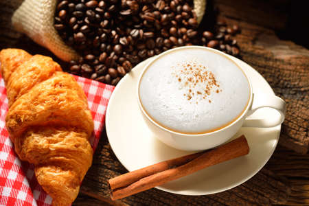 A cup of cappuccino with coffee beans and croissant  Stok Fotoğraf