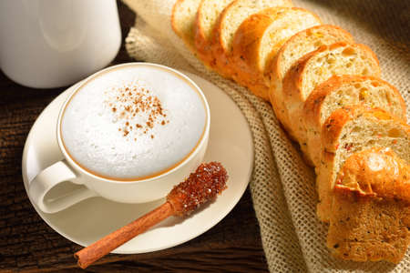 A cup of cappuccino and bread  photo