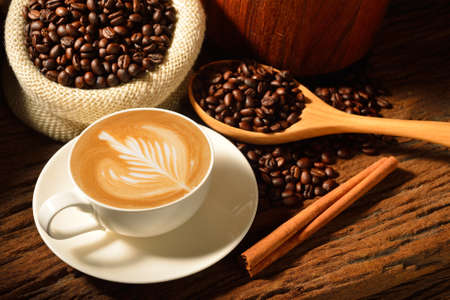 latte art: A cup of cafe latte and coffee beans Stock Photo