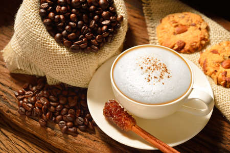 A cup of cappuccino with coffee beans and cookies photo