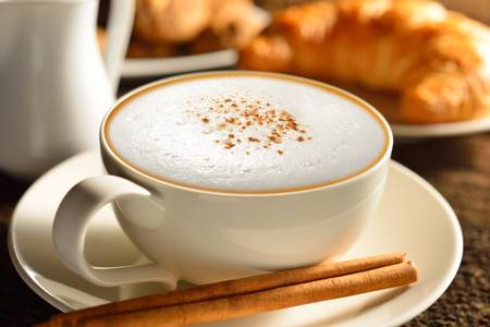coffee froth:  A cup of cappuccino and croissant