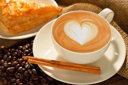 capuchino: Una taza de caf� con leche con granos de caf� y los pasteles de hojaldre