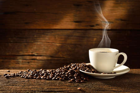 caffeine: Coffee cup and coffee beans on old wooden background Stock Photo