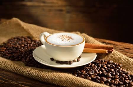 Eine Tasse Cappuccino und Kaffeebohnen