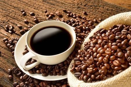 Coffee cup and coffee beans on old wooden background Stok Fotoğraf