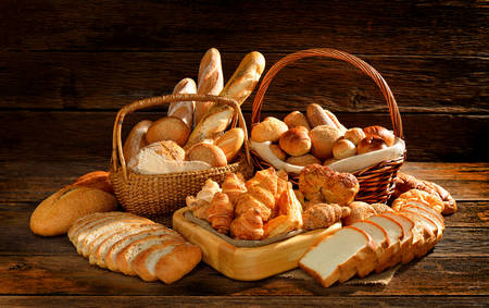 croissants: Bread and rolls in wicker basket on old wooden  Stock Photo