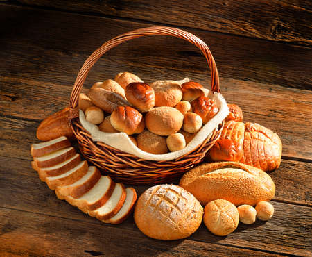 bread rolls: Bread and rolls in wicker basket on old wooden  Stock Photo
