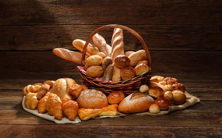 Variety of bread in wicker basket on old wooden