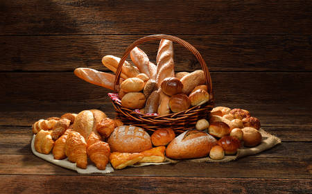 Variety of bread in wicker basket on old wooden  photo