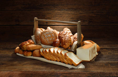 Variety of bread in basket on old wooden  photo