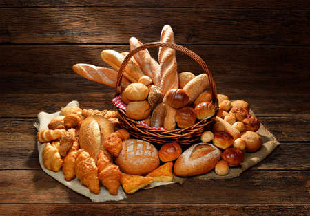 bakery products: Variety of bread in wicker basket on old wooden background  Stock Photo