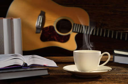 Cup of coffee with books and guitar on wooden table  photo