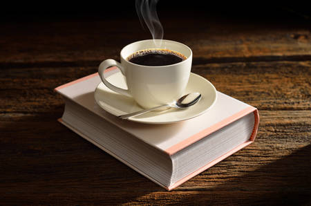 Cup of coffee with smoke on a book-like box