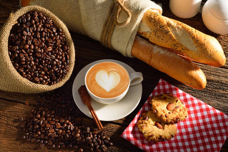 A cup of cafe latte with coffee beans and bread photo