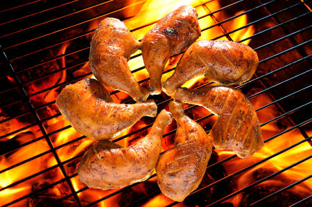 Grilled chicken thigh on the flaming grill photo