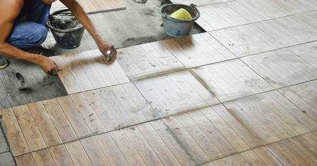 installation: Construction worker tiling the floor