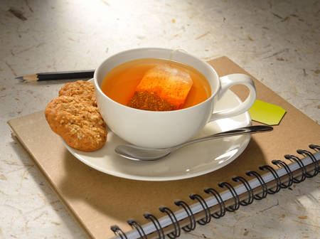 Cup of tea with tea bag and cookies on notebook photo